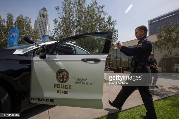 An LAPD officer makes a smart phone video at the unveiling of two new Ford Fusion hybrid pursuitrated Police Responder cars at Los Angeles Police...