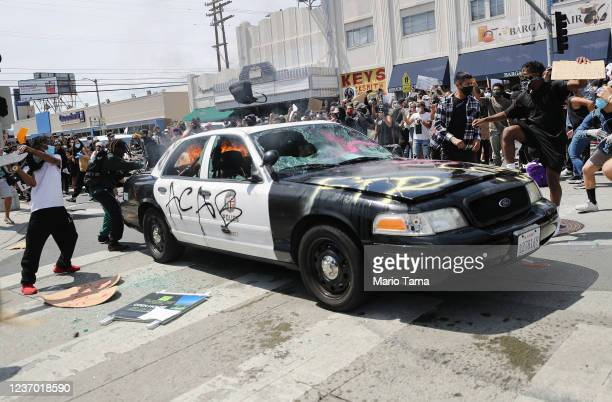 An LAPD vehicle begins to burn after being set alight by protesters during demonstrations following the death of George Floyd on May 30, 2020 in Los...