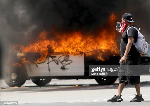 An LAPD vehicle burns after being set alight by protesters during demonstrations following the death of George Floyd on May 30 2020 in Los Angeles...