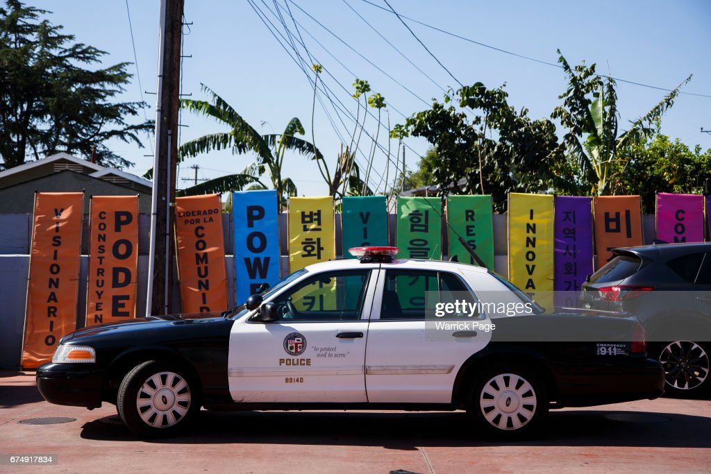 An LAPD vehicle is parked next to protest banners written in Korean and English for a peace rally to mark the 25th anniversary of the LA riots, at the intersection of Florence and Normandie, on April 29, 2017 in Los Angeles, California. Florence and Normandie was the flashpoint for the riots that was sparked by the police acquittals in the Rodney King beating.
