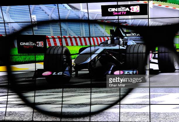 An LG Cinema 3D Smart TV display is partially seen through a pair of 3D glasses at the LG Electronics booth at the 2012 International Consumer...