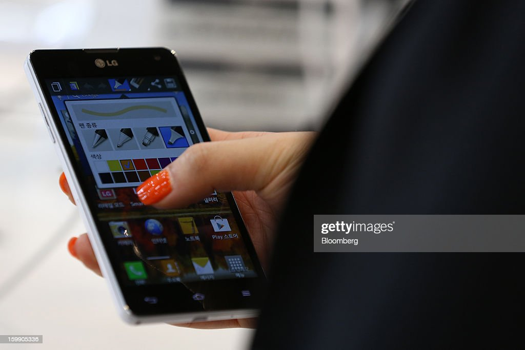 An LG Electronics Inc. Optimus G smartphone is held for a photograph at the company's flagship store in Seoul, South Korea, on Tuesday, Jan. 22, 2013. LG Electronics Inc. is scheduled to release fourth-quarter earnings on Jan. 30. Photographer: SeongJoon Cho/Bloomberg via Getty Images