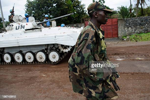 An M23 rebel walks down a street in Goma as an United Nations armoured personel carrier drives past, on the edge of Lake Kivu in the east of the...