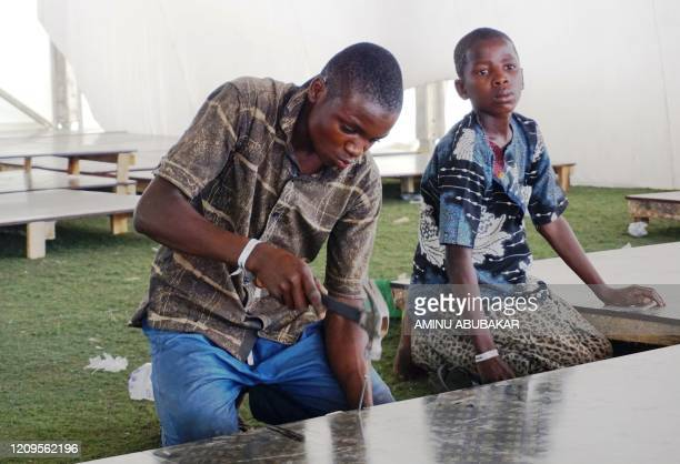 An man constructs wooden flooring at a COVID-19 coronavirus isolation centre at the Sani Abacha stadium in Kano, Nigeria, on April 7, 2020. - The...