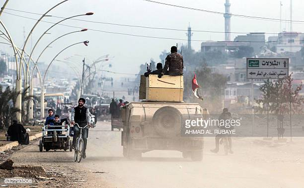 An man cycles past an Iraqi forces humvee driving on a street near the University of Mosul after government forces retook control of the area from...