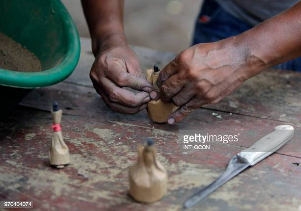 An man fills a makeshift cartridge with explosive material to make homemade mortar rounds to be used by anti government demonstrators in Masaya...