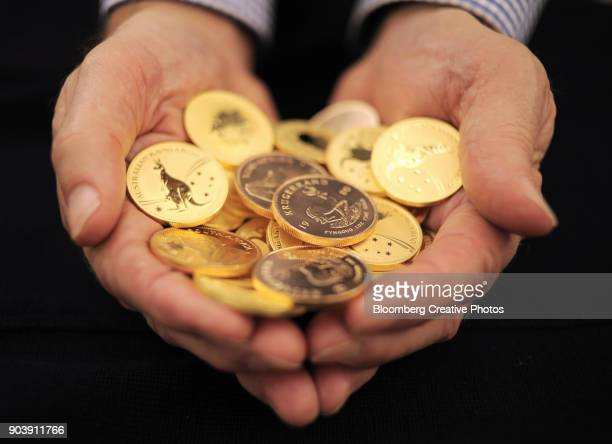 An man holds Australian gold sovereigns and South African gold Krugerrand coins