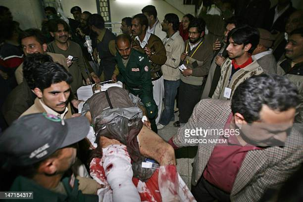 An man injured in the blast during the assasination of former Pakistani prime minister Benazir Bhutto is carried by her supporters at a hospital in...