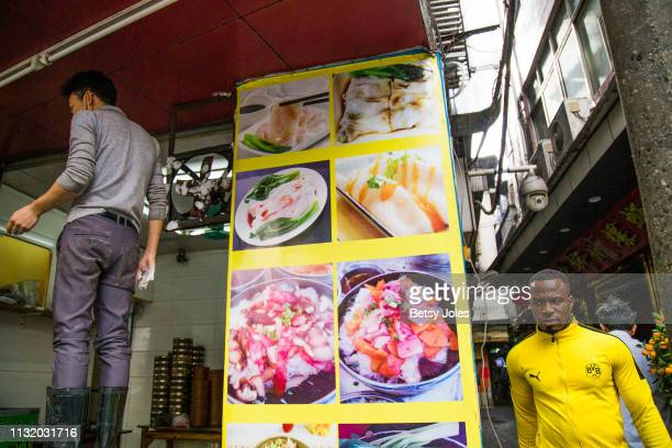 An man walks down a side street in Xiaobei, an ethnically diverse quarter of Guangzhou known as Little Africa on February 3, 2019 in Guangzhou,...