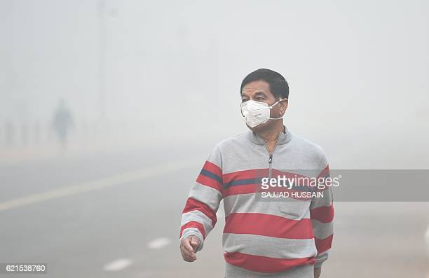 An man wears a mask as he walks along a road as heavy smog covers New Delhi on November 7 2016 Schools in the Indian capital will be closed for the...