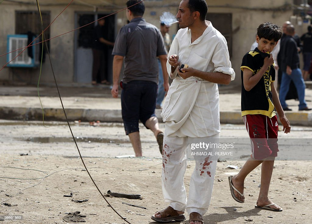 An man with blood on his pants smokes a cigarette at the scene of a car bomb explosion on April 23, 2010 in the impoverished Baghdad district of Sadr City. A series of five car bombs, three during prayers at Shiite mosques in Baghdad, and other attacks across Iraq killed 58 people, days after the government said Al-Qaeda was on the run.
