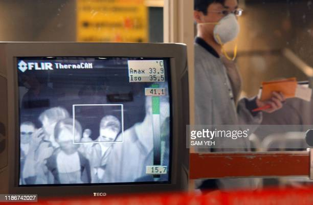 An masked passenger waits for his companions behind the window while a infrared scanner checks other passangers' temperature before departing at...