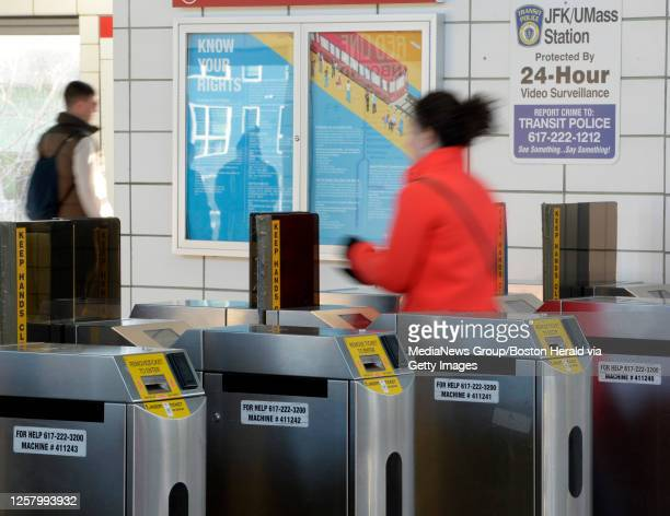 An MBTA passenger passes through automated fare collection gates at JFK/UMass Station in Boston, Massachusetts on April 4, 2019.