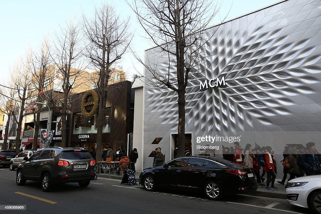 An MCM Holdings AG store, right, stands next to a Godiva Chocolatier Inc. store on Garosugil street in the Gangnam district of Seoul, South Korea, on Sunday, Dec. 22, 2013. Consumer prices climbed 0.9 percent in November from a year earlier after a 0.7 percent increase in October that was the smallest gain since July 1999. Photographer: SeongJoon Cho/Bloomberg via Getty Images