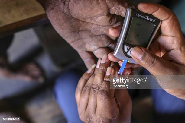 An member of the Jain Institute of Vascular Sciences medical team uses an Abbot India Ltd FreeStyle Optium glucometer to check the blood glucose...