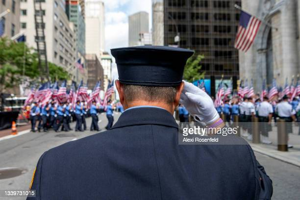 An Member of the New York City Fire Department salutes while American flags are marched during the FDNY Memorial Service at St. Patrick's Cathedral...