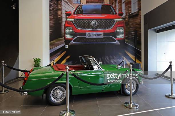 An MG Midget vehicle stands on display next to an advertisement for the MG Hector sports utility vehicle during the Hector's launch at the Morris...