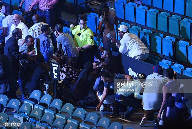 An MGM Grand security officer helps direct fans as they take cover behind a barricade inside the MGM Grand Garden Arena after the Floyd Mayweather Jr...