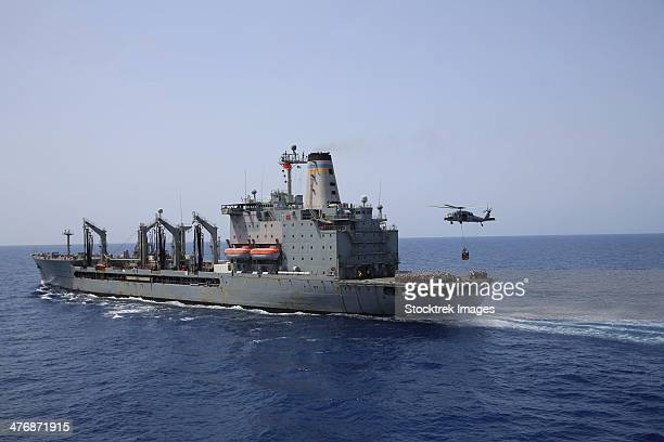 An MH-60S Sea Hawk conducts a vertical replenishment with USNS Laramie.