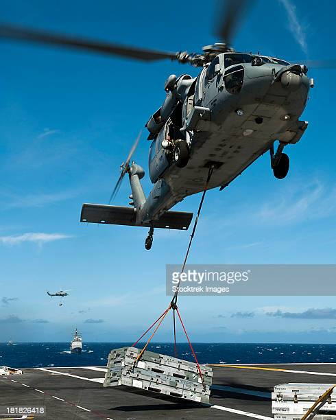 an mh-60s sea hawk helicopter lowers cargo onto the deck of uss john c. stennis. - helicopter stock pictures, royalty-free photos & images