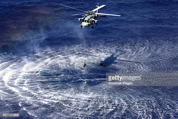 an mh-60s seahawk lowers a rescue swimmer into the water. - hovering stock pictures, royalty-free photos & images