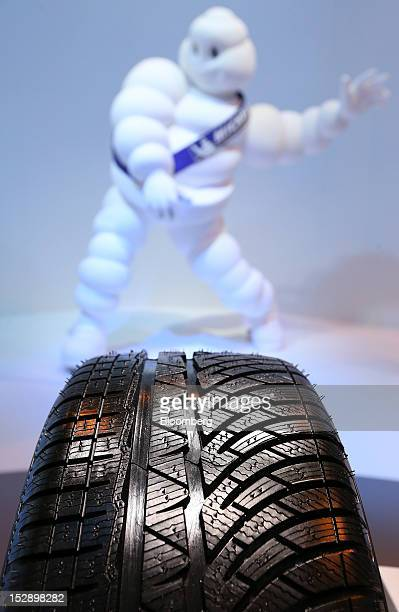 An Michelin Cie automobile tire stands on display in front of the company's 'Michelin Man' mascot on the second day of the Paris Motor Show in Paris...