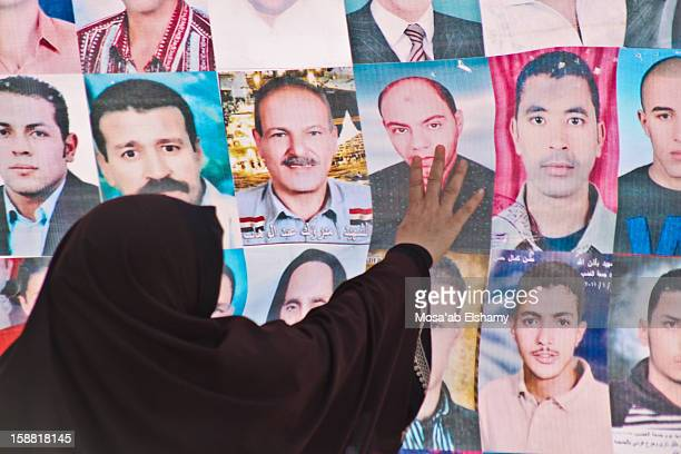 An mother of a victim who was killed during the January 25 revolution inspects a poster holding her son's photo in Downtown Cairo.