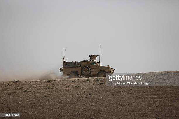 an mrap vehicle patrols the ridge of a wadi near kunduz, afghnanistan. - mine resistant ambush protected stock pictures, royalty-free photos & images