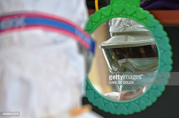 An MSF medical worker checks their protective clothing in a mirror at an MSF facility in Kailahun on August 15 2014 Kailahun along with Kenama...