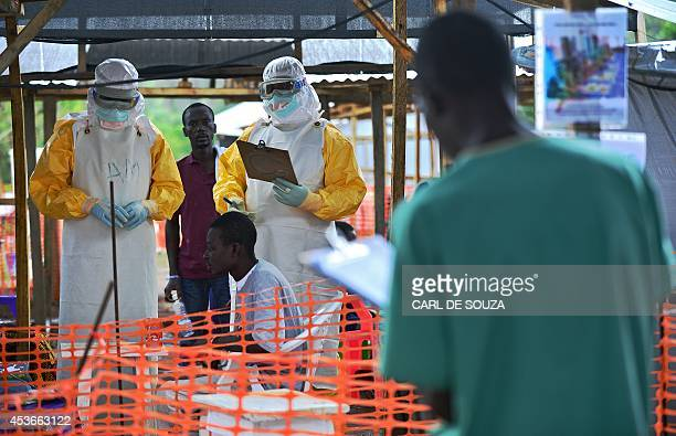 An MSF medical worker wearing protective clothing relays patient details and updates behind a barrier to a colleague at an MSF facility in Kailahun...