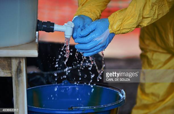 An MSF medical worker wearing protective clothing washes their gloves in chlorine at an MSF Ebola treatment facility in Kailahun on August 15 2014...
