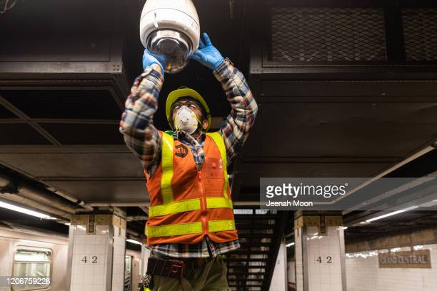 An MTA employee wearing a protective mask cleans a subway security camera at Grand Central Terminal on March 12 2020 in New York City US President...