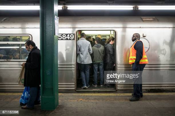 An MTA worker looks on as people stand on an idling train at the HoytSchermerhorn subway station April 21 2017 in the Brooklyn borough of New York...