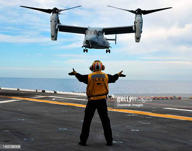 An MV-22 Osprey tiltrotor aircraft approaches the flight deck.