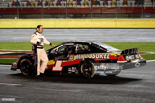 An NASCAR official stands next to Mike Bliss driver of the Miccosukee Indian Gaming Resort Chevrolet in his car on pit road in a rain delay during...