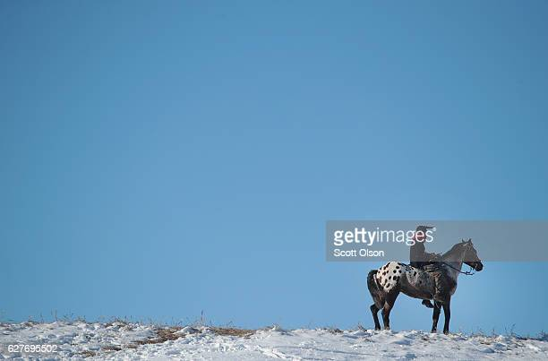 An Native American activist rides along a ridge which overlooks Oceti Sakowin Camp on the edge of the Standing Rock Sioux Reservation on December 4...