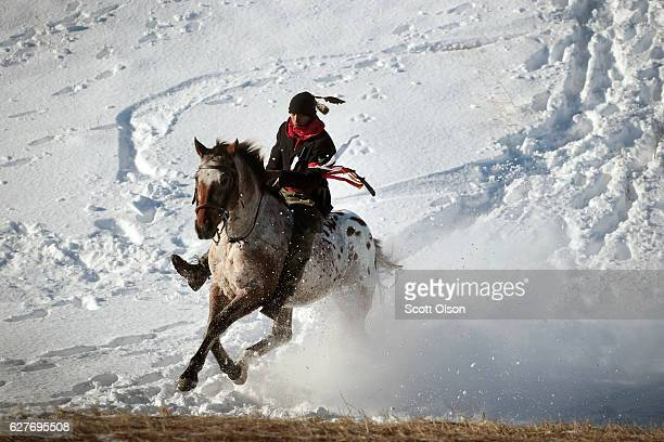 An Native American activist rides down fom a ridge which overlooks Oceti Sakowin Camp on the edge of the Standing Rock Sioux Reservation on December...