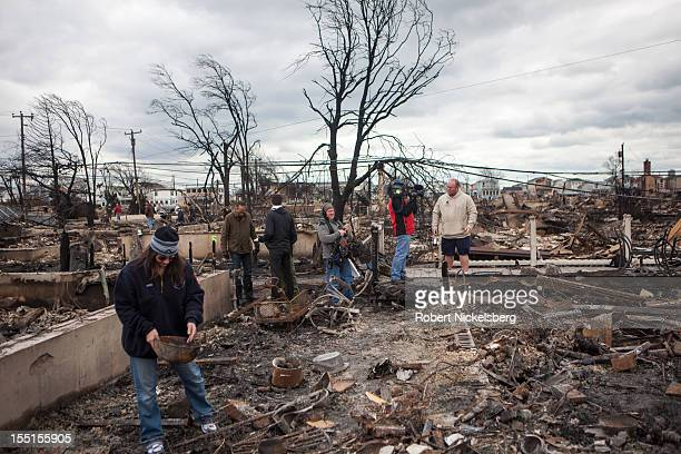 An NBC Television camera crew films Kieran Burke, right, a FDNY fire marshal and resident of Breezy Point whose home was burned November 1, 2012...