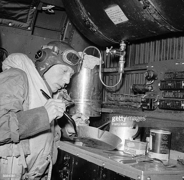 An NCO signaller with 228 Squadron of Royal Air Force Coastal Command at St Eval in Cornwall cooks for the crew in the galley during a flight