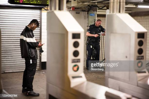 An New York Police Department officer stands guard in the Franklin Avenue subway station amid a rise of gun violence in the Brooklyn borough of New...