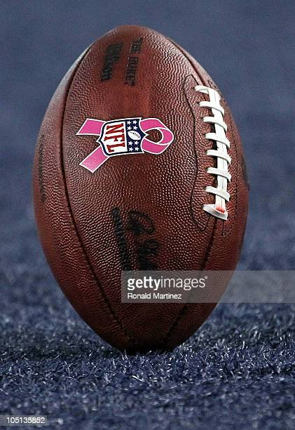 An NFL logo with a pink ribbon for Breast Cancer Awareness month on a football between the Tennessee Titans and the Dallas Cowboys at Cowboys Stadium...