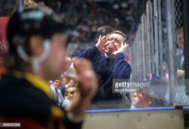 An NHL fan makes funny faces at an unidentified player who sits in the penalty box during an NHL preseason game in September 1991