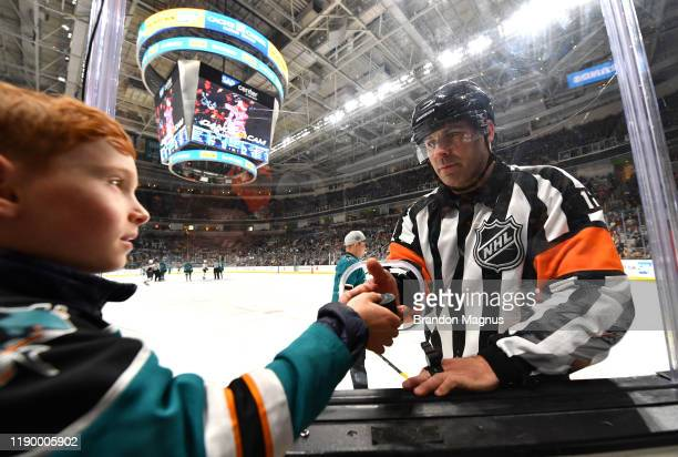 An NHL referee gives a fan a puck at SAP Center on December 21 2019 in San Jose California