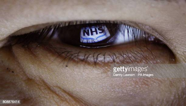 An NHS logo is reflected in an eye to illustrate a new NHS scheme that will invite participants turning 40 years old to assess their own health check...