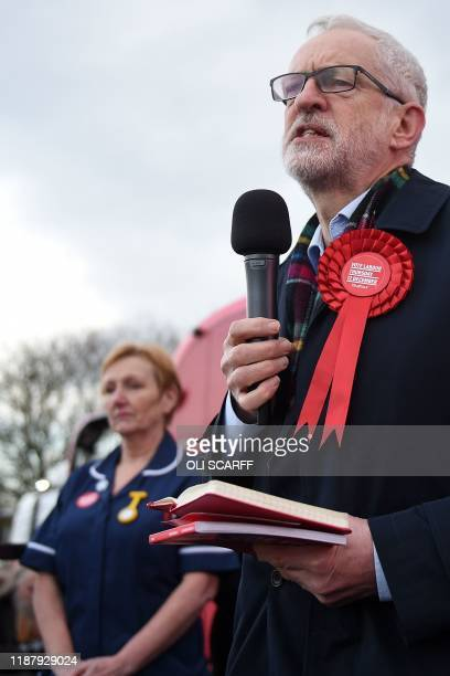 An NHS nurse stands on the platform with Labour supporters as Britain's Labour Party leader Jeremy Corbyn speaks during a general election campaign...
