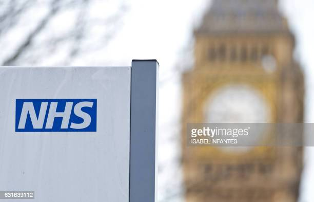 An NHS sign is pictured at St Thomas' Hospital in front of the Big Ben clock face and the Elizabeth Tower on January 13 2017 in London The Red Cross...