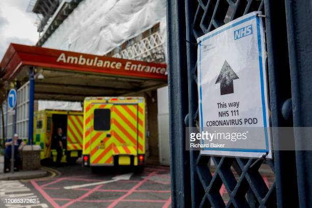 An NHS sign points towards a Coronavirus testing pod as an ambulance arrives at the AE Department of Kings College Hospital in Camberwell south...