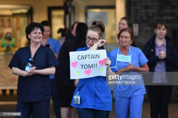 An NHS staff member wipes her eyes as she holds a sign to thank British veteran Captain Tom Moore who raised over 13 million GBP for the NHS as they...