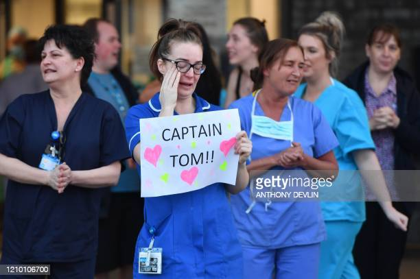 TOPSHOT An NHS staff member wipes her eyes as she holds a sign to thank British veteran Captain Tom Moore who raised over 13 million GBP for the NHS...