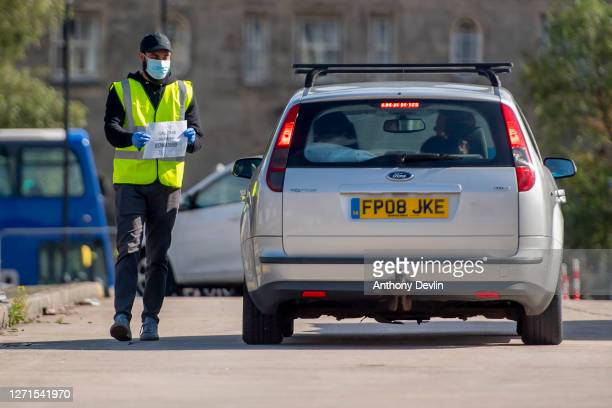 An NHS Test and Trace staff member holds up a sign as a car arrives at an NHS Covid Testing facility in Bolton town centre as Coronavirus...